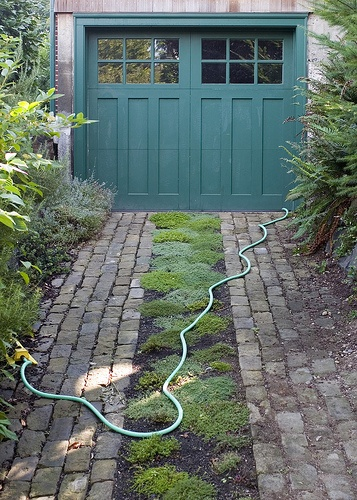 Brick driving strips allow low ground covers to be planted in between. The color and style of the garage door make this a particularly nice combination