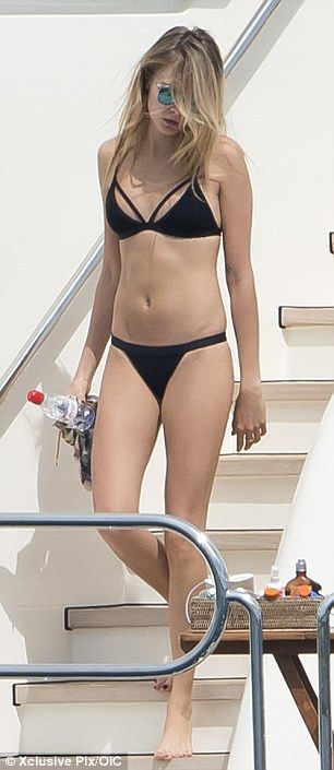 Looking good: Cara displayed her washboard abs as she lounged around on the yacht...