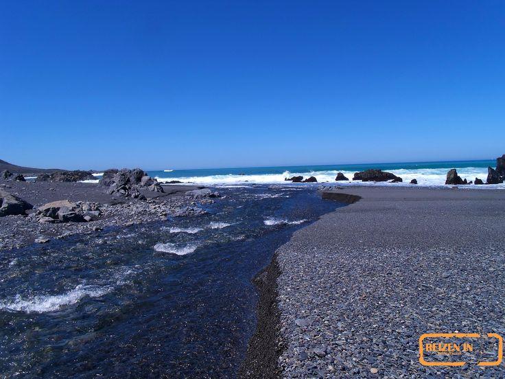 Zoet water stroom de zee in op een ruig strand net buiten Wellington.