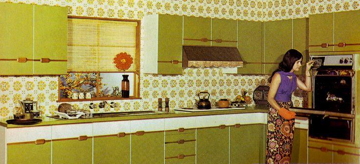 1970 avocado groene keukenkastjes met behang erachter.