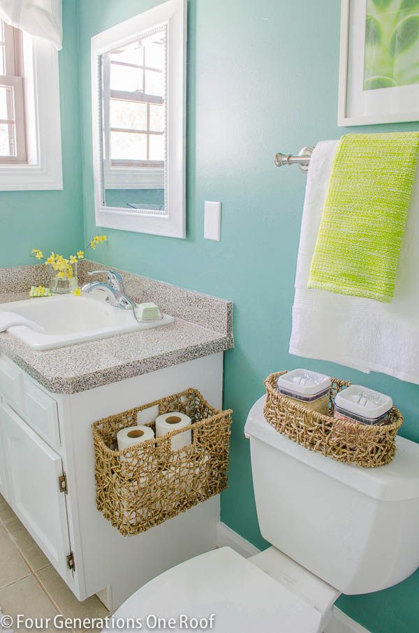 Green Bathroom makeover with simple basket additions from HomeGoods. Love the idea of using a basket to hold toilet paper!