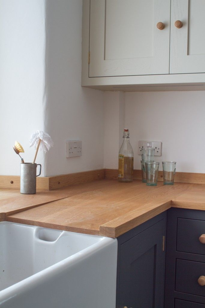 Sustainable Kitchens - The Cosy Stone Cottage Kitchen in Bath. Farmhouse sink surrounded by an oak worktop creates the perfect country feel in this shaker style oak kitchen. The base units are painted in Farrow & Ball Down Pipe while the wall units are painted in Farrow & Ball Shaded White.