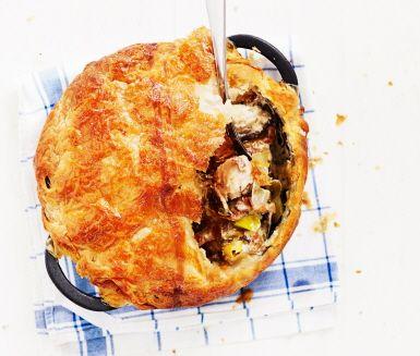 Smördegspaj med kycklinglårfilé, bacon, purjolök, vitlök och svamp, gräddad i gryta. Bryn ingredienserna och rör ner crème fraiche och grädde. Lägg över ett lock av smördeg och grädda pajen i ugn. Grytan och smördegslocket ger en särskilt smakrik paj – lika god till vardag som fest.