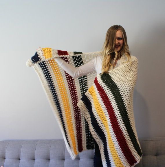 This handmade Hudson Bay inspired blanket is crocheted with 100% acrylic (vegan) yarn. It is an off-white blanket crocheted with blue, yellow,