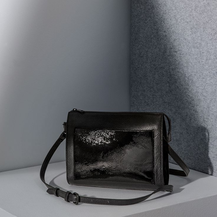 A modern yet timeless sling bag in pebble-grain leather with suede and patent leather detailing and a detachable crossbody strap for added versatility.