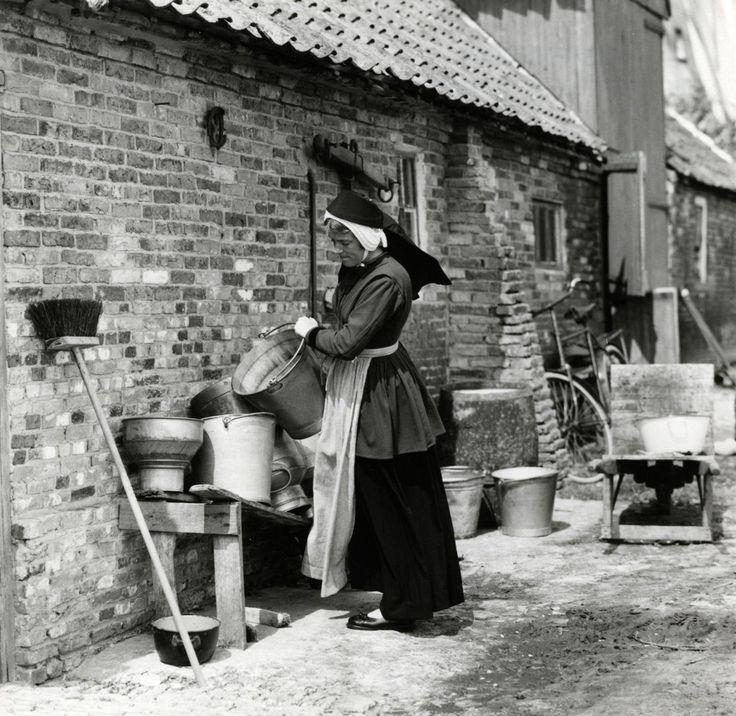 Vrouw in klederdracht naast een boerderij op Terschelling, waar een bezem tegen staat geleund, in de weer met emmers en melkbussen, Formerum 1956.
