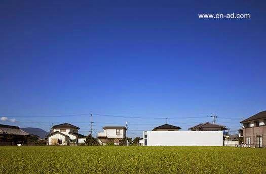 Minimalist small japanese house - Vista de la casa a la distancia evidencia la integración con el entorno. Es una vivienda pequeña con forma de prisma rectangular.