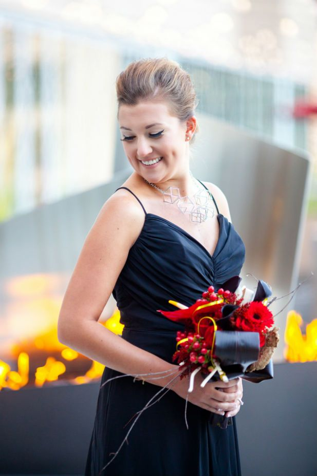 Modern bridesmaid look with geometric necklace, black gown, and red and black bouquet