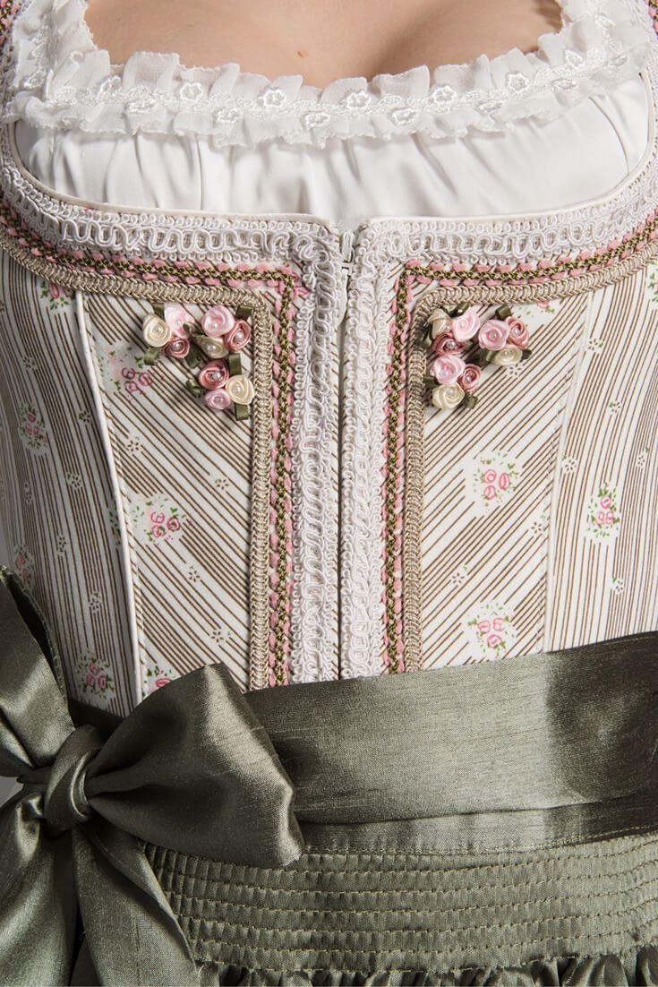 """Pastelfarben und feminine Eleganz beschreiben dieses Hochzeitsdirndl von Krüger Feelings. """"Nelia"""" schimmert in leichtem Creme Grün und die edlen Borten machen diesen Braut Look komplett."""