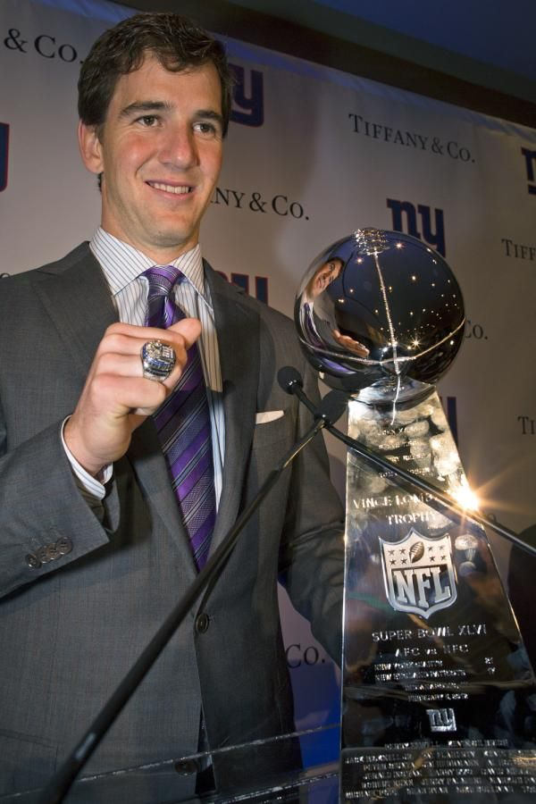 Eli Manning with his ring and trophy