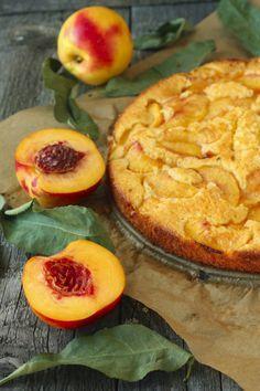 Det här är en underbar paj med mandelkräm och persikor som serveras på hallonspegel och lättvispad grädde.