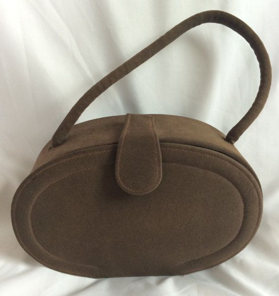 Vintage brown hardcase purse, oval shaped. The purse has a short handle and a clasp. The interior of the purse is bare except for a small mirror.