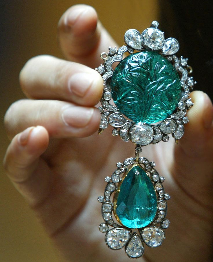 Historic Emerald and Diamond Pendant Brooch - Mughal, emerald early to mid 17th century, brooch 1829 - The near circular convex emerald of exceptional colour and clarity weighing 55.8 carats with superb Mughal carving of tulips on both sides, the top and bottom with delicately carved protruding drill holes, the old-cut diamond scroll frame with a three-stone cluster above and below the carved emerald, suspending a detachable pierced drop-shaped emerald..