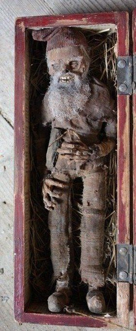 "Swedish Hustomte: The Naturally mummified body of a swedish ""Hustomte"" or housegnome. dated 1866 ~Hustomten comes from scandinavian folklore and is a gnome that is said help the farmer and cares for the lifestock, he has a fierce temperament and is very traditional. If he gets upset he will bring misery to the household ~The label reads- ""This litte housegnome was found by my father, Jan Peter Peterson, in the winter of 1866 inside the old barn wall. He was already lifeless ~ By Jacob…"