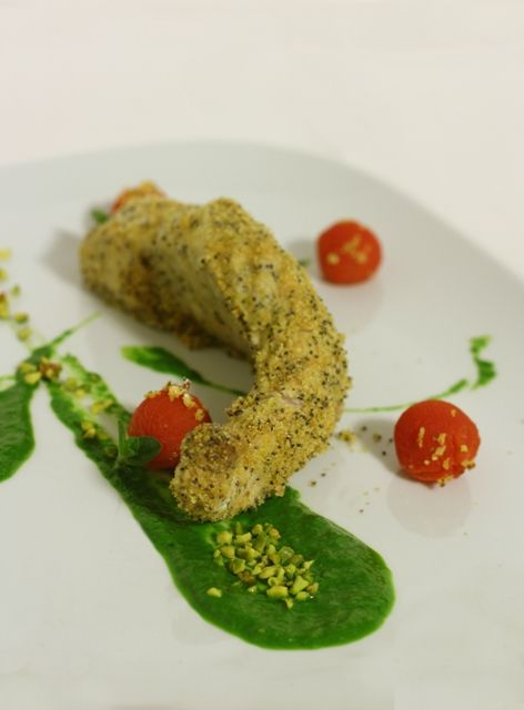 Sturgeon filet baked in the oven with poppy seed and pistachio.     A fish with delicious taste, enriched by rocket cream and baby tomato confit.