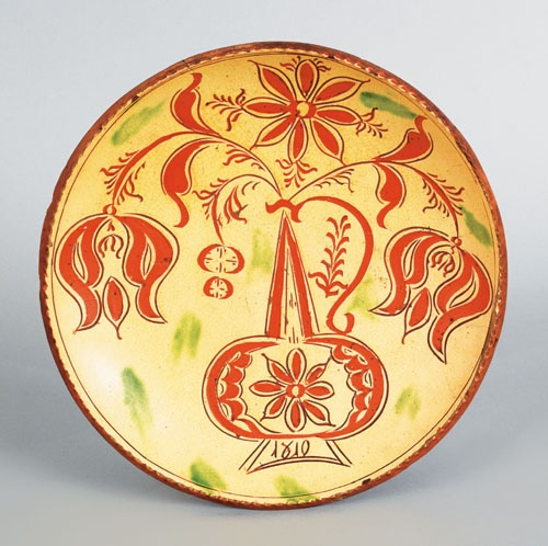 "Realized Price: $ 52140 Haycock Township, Pennsylvania sgraffito decorated redware charger dated 1810, attributed to Conrad Mumbouer, with tulips and leaves emanating from an urn, all on a yellow glaze background with green splotches, 12"" dia."
