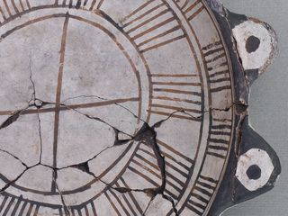 El cuerpo es semiesférico, la base plana, y el borde directo con labio convexo, al que se adhieren dos pares de protuberancias opuestas, que simulan ojos y patas. No se ven huellas claras de uso. Está fracturada en la porción izquierda y fue restaurada. Esta pieza es gemela de la n° 00152. Se obtuvo en 1964 en excavaciones realizadas por la Sociedad Arqueológica de Ovalle (tumba VII, vasija 7).