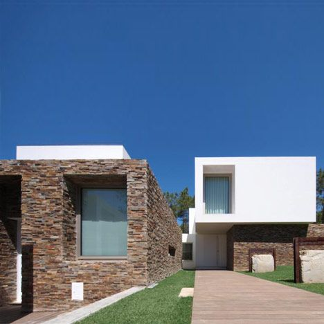 This house by Portuguese studio Jorge Mealha Arquitecto features white rendered volumes sat atop a stone structure, located by a beach on the outskirts of Lisbon, Portugal.