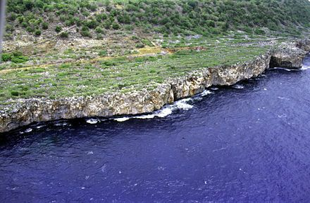 Navassa Island - Aerial photo showing the steep rocky coast that rings the island.