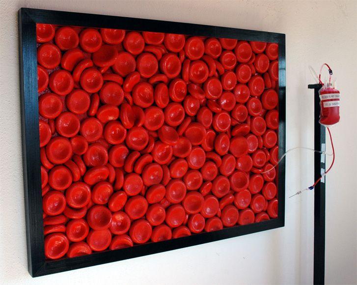 """YOU CAN'T MAKE BLOOD MINOLITI Installazione artistica, polistirene e legno, 125x95x12cm(profondità), sacca con supporto in legno 150cm (altezza), 2014. L'installazione artistica """"you can't make blood"""" è costituita da 2 parti che interagiscono tra loro: globuli rossi fluttuano e riempiono la sacca del prezioso fluido. La materia da principio plasmata diviene energia vitale, che preservata è pronta a rinnovarsi continuamente."""