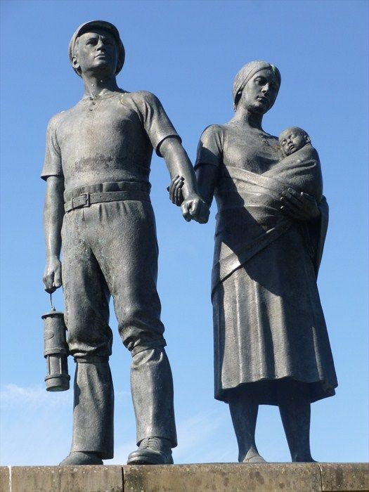 A bronze lifesize sculpture of a Welsh Coal Miner and his Family - located between Llwynypia and Tonypandy, in the Rhondda Valley, Wales. The miner is carrying a Davy Lamp and the women is carrying her baby 'Welsh fashion'.