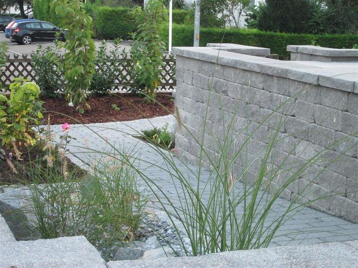 Weg aus Pflastersteinen umrahmt von einer Gartenmauer