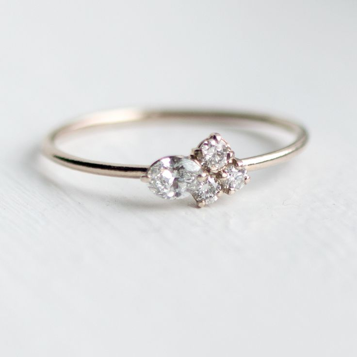 This delicate mini cluster ring features a cluster of four sparkling genuine white diamonds in prong setting, on top of a very delicate smooth slim band. This handmade asymmetrical cluster ring will b