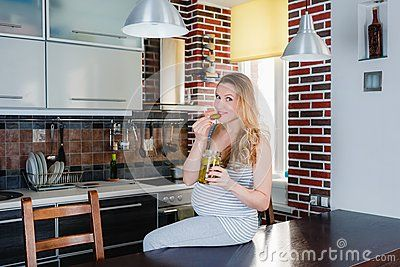 The smiling pregnant woman in kitchen is eating pickle. Healthy food.