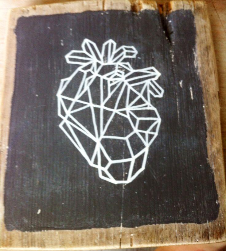 Oud steigerhout met krijtbordverf. Geometrisch anatomisch hart met krijtstift erop getekend. Mooi contrast: strakke geometrische vorm op  oud hout.