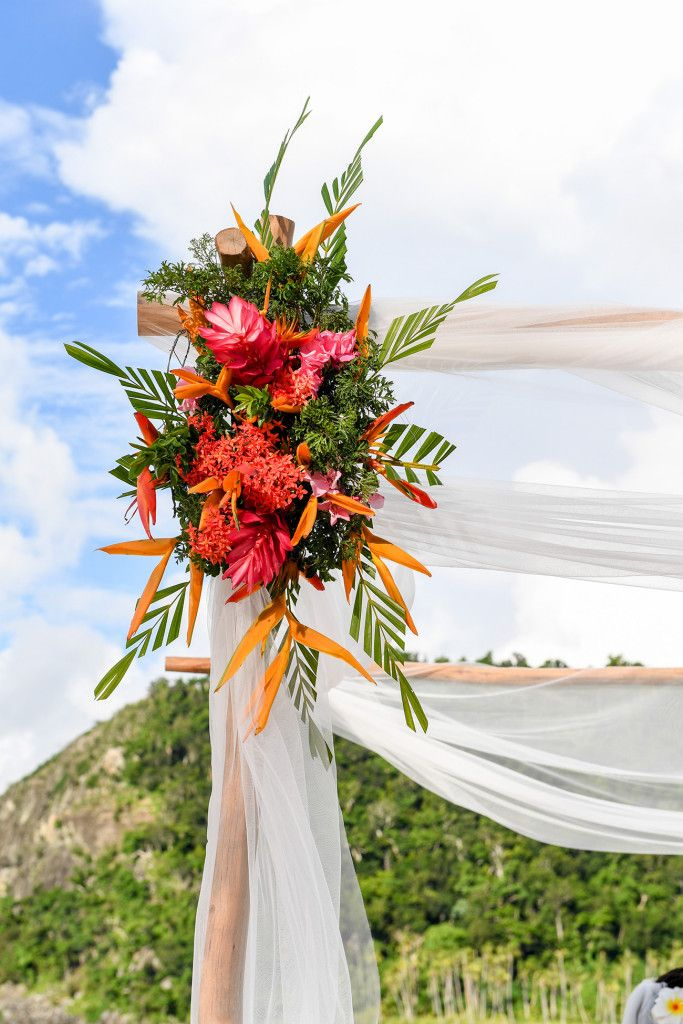 Tropical flowers on the wedding arch Paradise Cove Island Resort, Yasawa, Fiji. Photographed by Anais Photography.