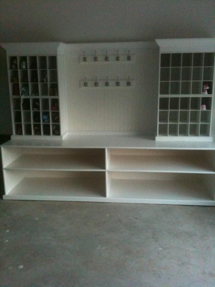 Garage mud room - hooks for backpacks and umbrellas, storage for small shoes in cubbies, shelves at the bottom for tennis shoes and boots.