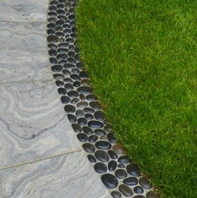 Black pebbles set in concrete as the paving border. Could also work between paving slabs.