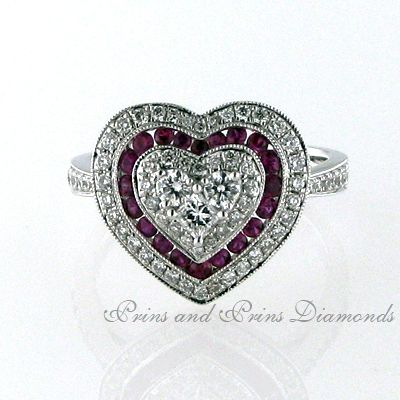 There are 20 = 0.34ct round cut rubies and 68 = 5.90ct GH/VS – SI round brilliant cut diamonds channel and pavé set in a heart shaped design, set in 18k white gold