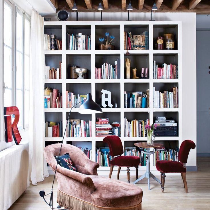 """Dans ce coin bibliothèque accueillant, Igor-David Becker a réalisé de nombreux meubles, comme cette pièce mécanique, """"à volant d'inertie"""", transformée en guéridon à hauteur réglable et la bibliothèque en carreaux de plâtre, où sont exposés des objets hétéroclites. Les fauteuils de théâtre en velours rouge ont été chinés. Méridienne en cuir vintage."""