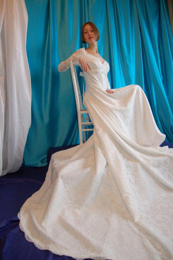 Кружевное платье молочного цвета силуэта ампир со шлейфом, длинный рукав, расшитая бисером, пайетками и жемчугом аппликация под грудью, спинка застегивается на прозрачный кнопки, шлейф подстегивается на пуговицу и имеет петлю для носки в руке.