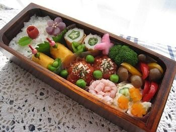 たっぷりおかずで華やかなお弁当♪メインのミートボールのトマト煮を中心として、ピックの刺さった卵焼きにお花型のにんじんやハム、緑のスナップエンドウなど、色とりどり。スリム形は1辺が短いので、その分おかずをきっちり詰めやすいのもいいところ。