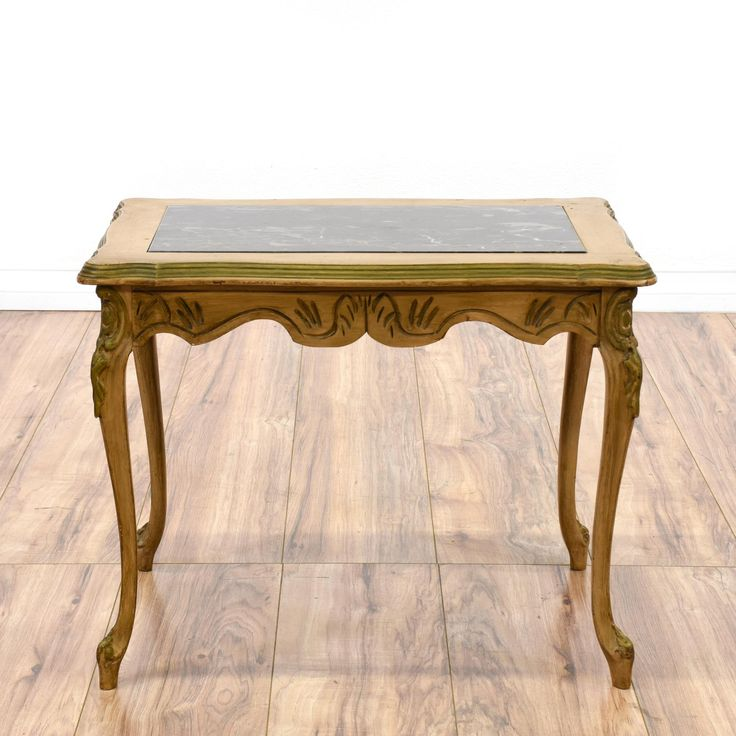 This French Provincial side table is featured in a solid wood with a distressed oak finish. This cottage chic end table has a black marble top, carved sabre legs and beveled edges. Perfect for displaying flowers! #cottagechic #tables #endtable #sandiegovintage #vintagefurniture
