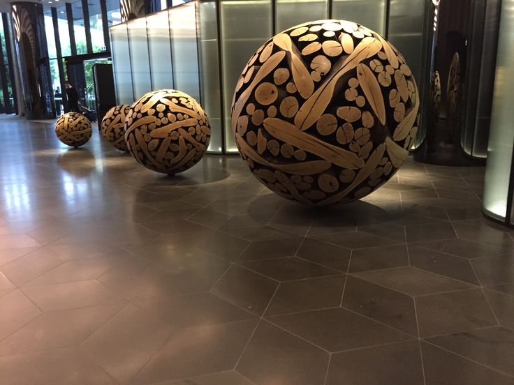 PHOTO THREE: These are several burnt timber balls, in the crown metrople hotel lobby. Placed in size order from smallest to largest, they are used as a unique piece of art work.
