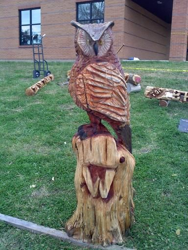 Pin chainsaw carving of an indian in wolf head dress made