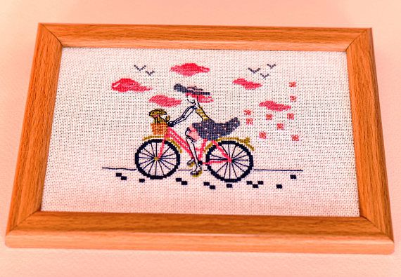 Framed hand embroidered wall art pretty girl on a bicycle