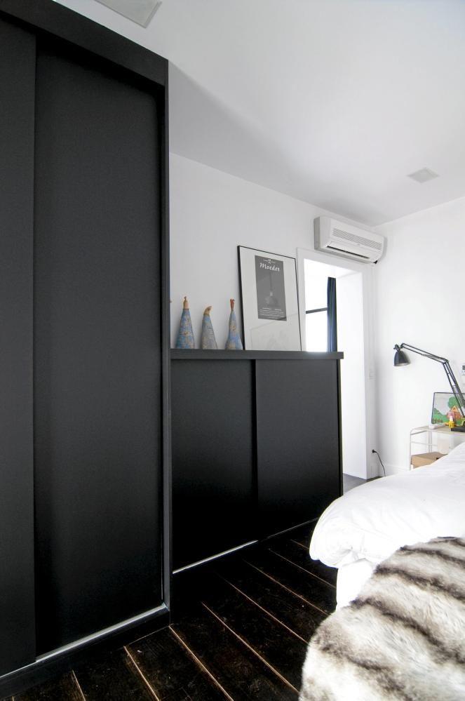 Soverommet er mørkt på bunnen og lyst på toppen. Fargen i tregulvet dras oppover mot taket ved hjelp av enkle, svarte skap med skyvedører. Både vegger og tak er holdt i hvitt, med matchende sengetøy.
