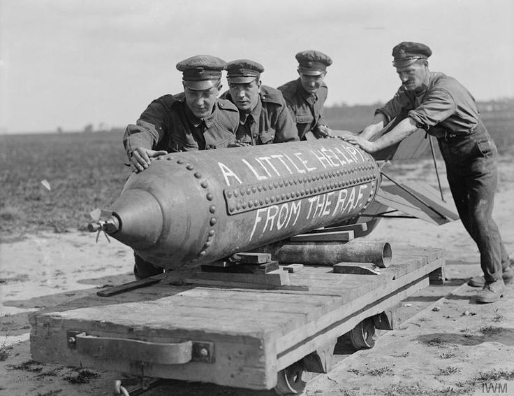 """Air mechanics of No. 207 Squadron RAF moving a big bomb by rail-trolley to load it on to a night bombing aeroplane. Ligescourt, 29 August 1918. The caption on the bomb reads: """"A little hell pie from the RAF."""