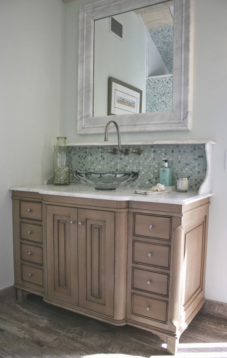 These great floors look like weathered wood, but it's really tile.  Love the mosaic back splash that makes the sink vanity look reminiscent of an English-style antique washstand.