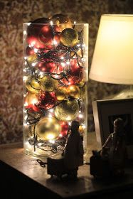 Hallway Christmas decor - old ornaments with twinkle lights in a large glass vase/jar