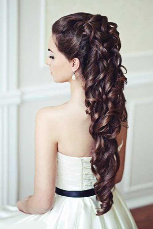 On peut dire que cette mariée a de vrais cheveux de princesse : ils lui arrivent jusqu'en bas du dos ! Mais rassurez-vous, cette coiffure peut tout aussi bien être réalisée sur des cheveux moins longs. Ils sont attachés assez hauts sur la tête, avec du volume, et tombent ensuite en une gigantesque cascade de très belles boucles brunes, qui tournent sur elles-mêmes. Cette coiffure est à éviter si vous avez choisi de porter un bouquet de fleurs en cascade, pour ne pas faire « too much » !