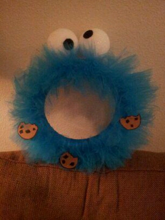 I found a halloween monster wreath on pinterest and I just made it my own by creating eyes and cardboard cookies then glued this on... my hubby made the cookies (gotta give him his credit)... or next project will be elmo :)