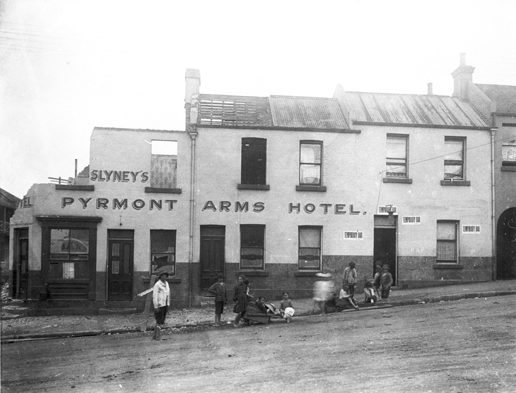 The former Pyrmont Arms Hotel – Photo taken in 1914: Two-storey split level rendered and painted sandstone and corrugated iron roof building in final stages of demolition. Near the entrance, over which hangs an ornamental gaslamp, is a sign 'Temporary Bar'. In the roughly tarred roadway a group of children play. Photo courtesy of City of Sydney Archives.  #sydney #cityofsydneyarchives #history #archives #pyrmont