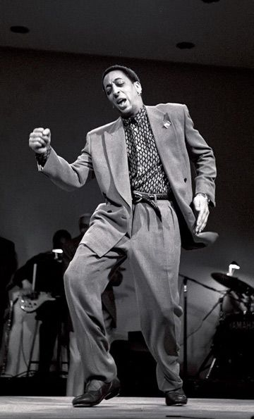 """Gregory Hines - began tapping at three. An avid improvisator of tap steps, tap sounds, and tap rhythms. """"He purposely obliterated the tempos, throwing down a cascade of taps like pebbles across the floor.  In those moments he aligned tap with the latest free-form experiments in jazz and new music and postmodern dance.""""  Responsible for National Tap Dance Day.  Died in 2003 at 57 of liver cancer."""