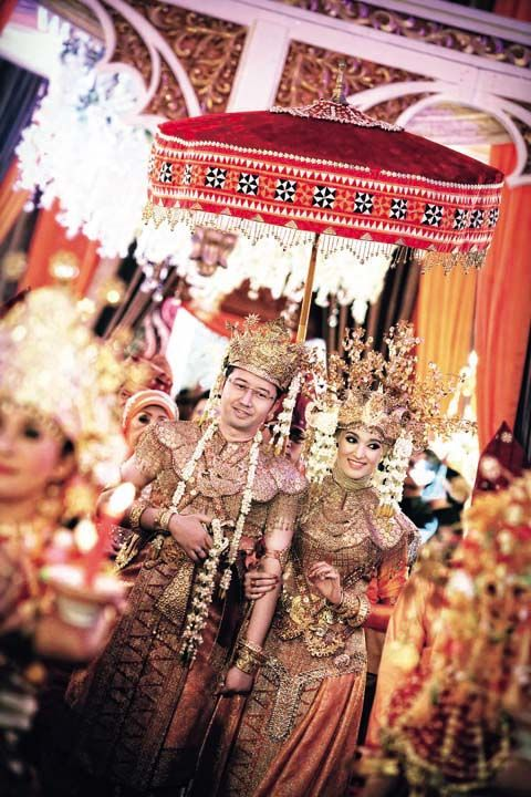 A wedding couple, in traditional Palembang wedding costume (from Southern Sumatra Province, Indonesia) ceremoniously entered the wedding hall.