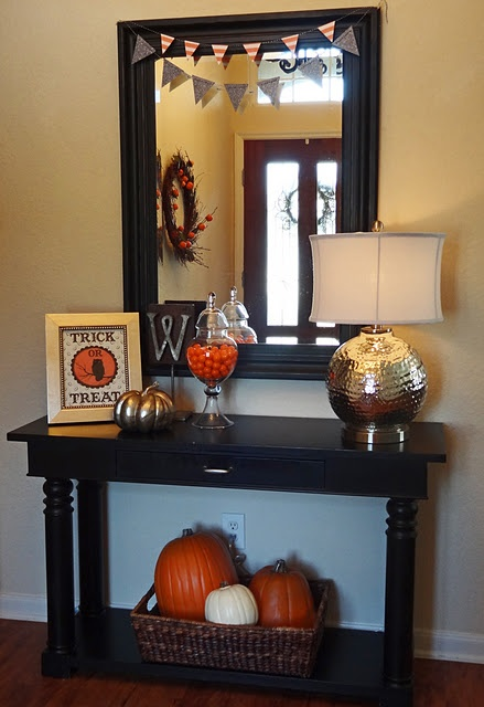 Pumpkins in a basket on bottom shelf of console table... Probably fake pumpkins. Candy dish on top of table.: